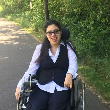 Young Latina wheelchair user with glasses and long dark hair. Photo is of her outside on a sunny day