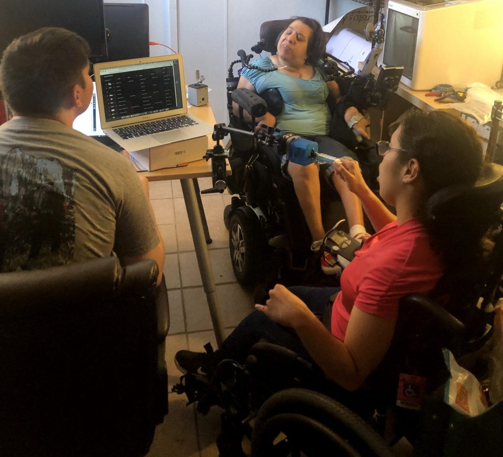 Elijah, Adriana and Cristina chatting by a table with a laptop on it. Both Adriana and Cristina are wheelchair users